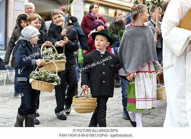 14 April 2019, Bavaria, Bad Tölz: During the Palm Procession on Palm Sunday, children walk through the city centre and carry palm bushes in their baskets