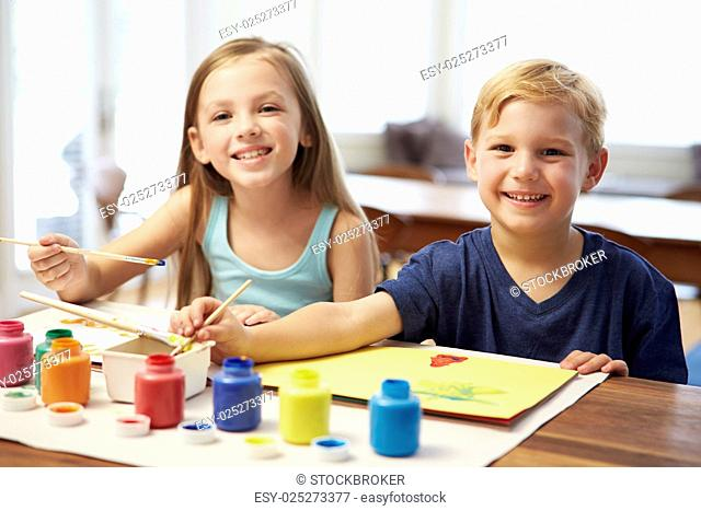 Two Children Painting Picture At Home