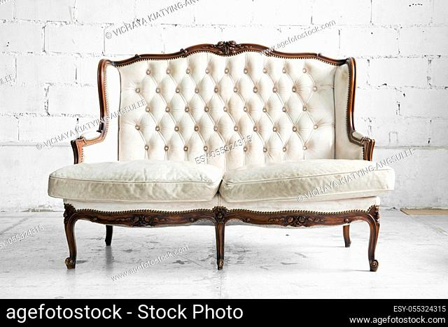 White genuine leather classical style sofa in vintage room