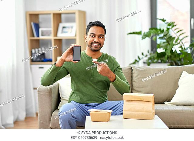 indian man using smartphone for food delivery