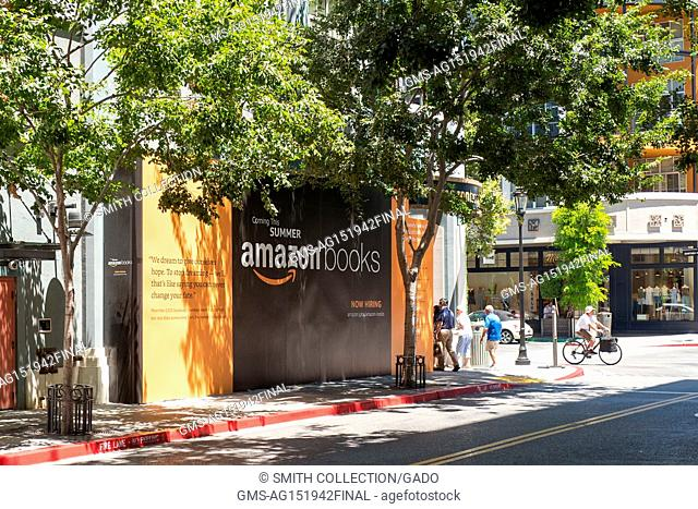 Visitors walk and bike past signage announcing a new Amazon Books physical retail store at Santana Row, an upscale shopping center in the Silicon Valley town of...