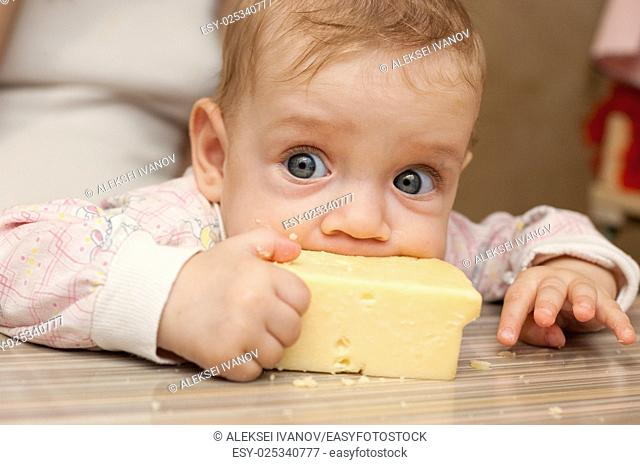 The baby sucked his lips to a large piece of cheese