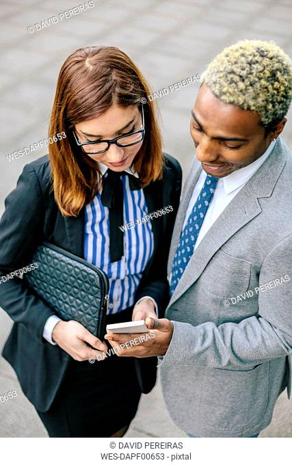 Young businessman and woman looking at smart phone