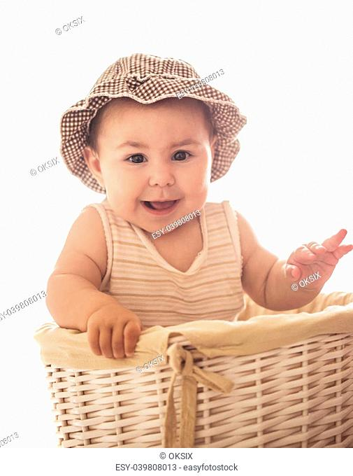Eight month baby girl play with laundry basket, isolated on white