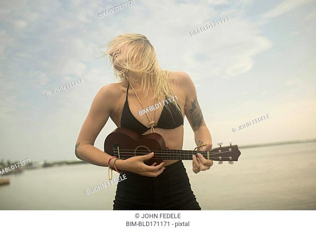 Caucasian woman playing ukulele on beach
