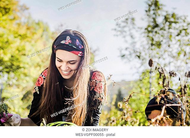 Happy young woman gardening