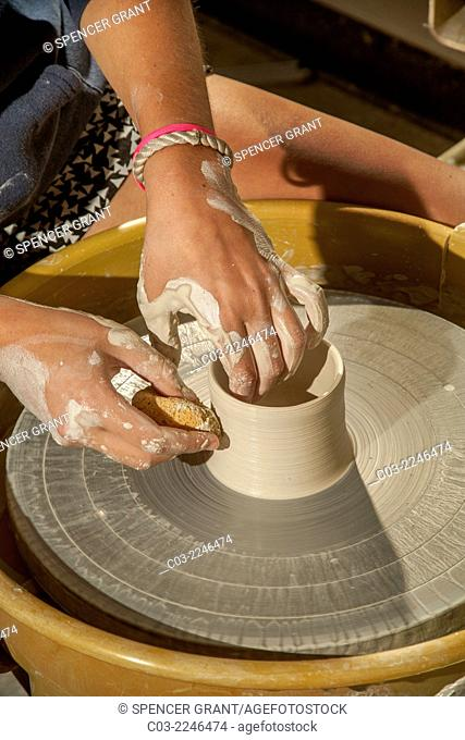 A clay pot is spun on a potter's wheel in a high school pottery class in San Clemente, CA. Note sponge to shape the moist clay