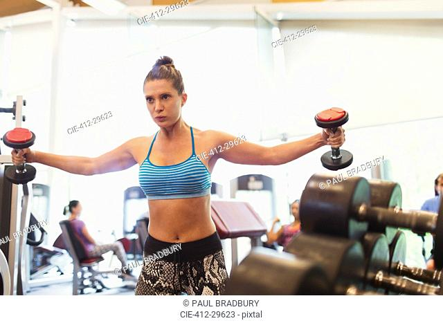 Focused woman doing dumbbell chest fly at gym