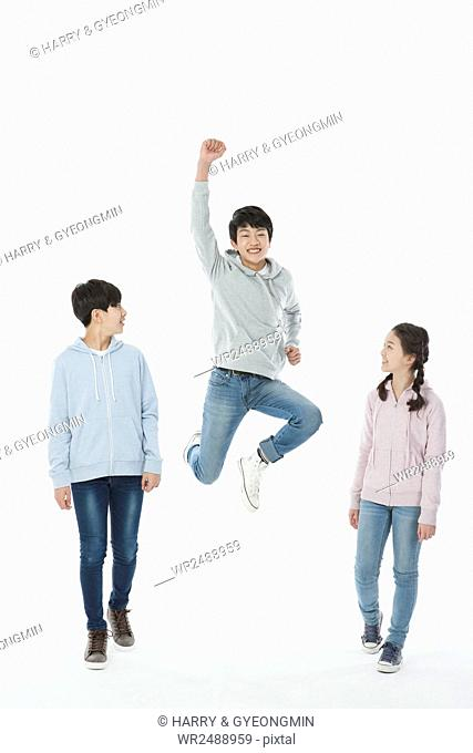 Smiling boy jumping and his friends watching him