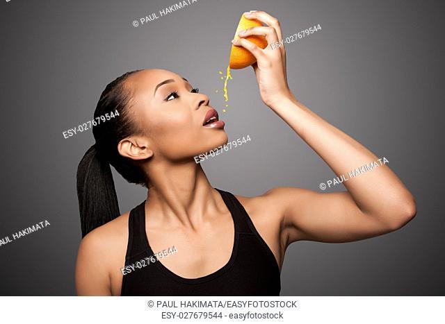 Beautiful healthy happy black asian woman squeezing delicious orange juice mandarin fruit