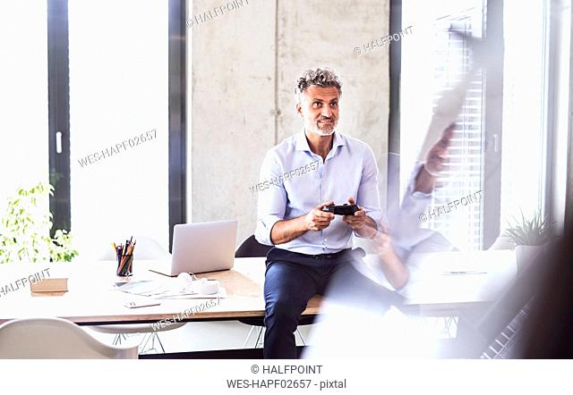 Smiling mature businessman sitting on desk in office using controller