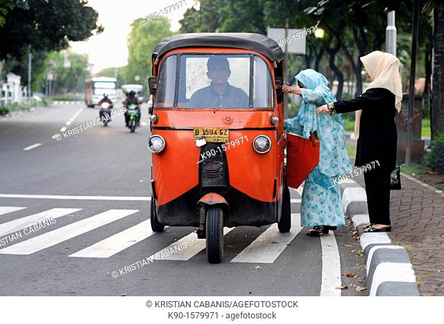 Two muslim women with head cover, standing at the street and getting into a bajai, open door, Jakarta, Java, Indonesia, Southeast Asia