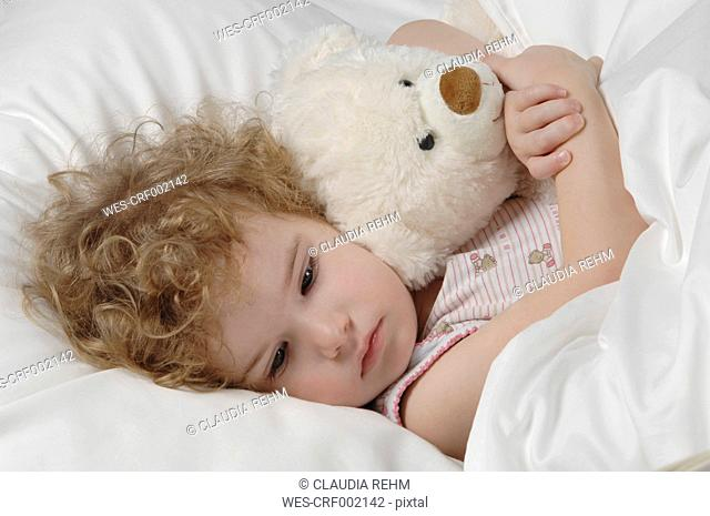 Sick girl lying in bed with teddy bear
