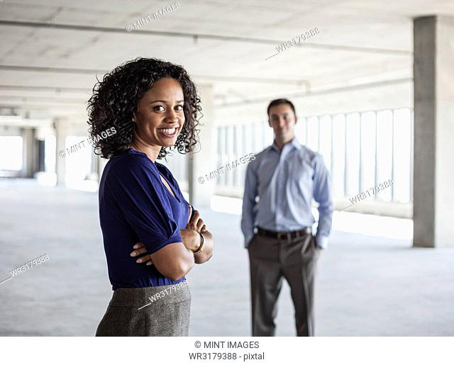 Mixed race team of business people in a large empty raw office space
