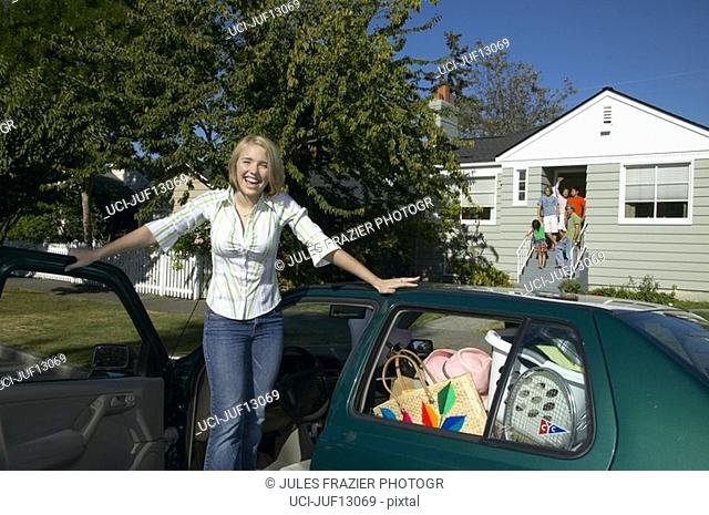 Young woman standing beside packed car