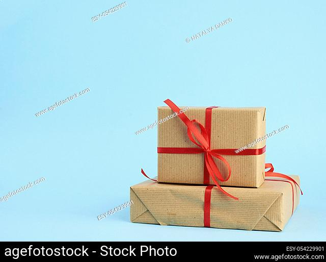 stack of boxes wrapped in brown paper and tied with a red bow, gifts on a blue background, place for text