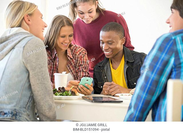 Teenagers using cell phone at table