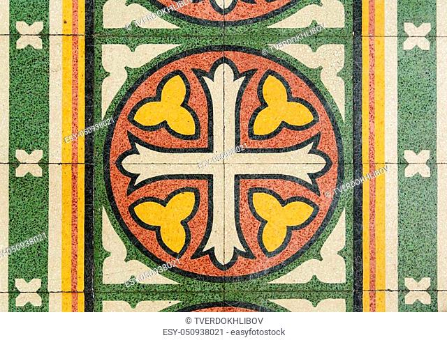 tiles on the floor in an ancient form of a cross and floral ornament