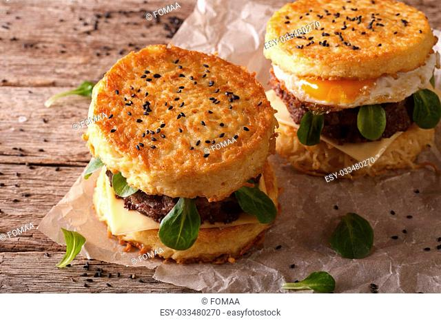 Ramen burgers with beef and egg on a paper on a wooden table. Horizontal