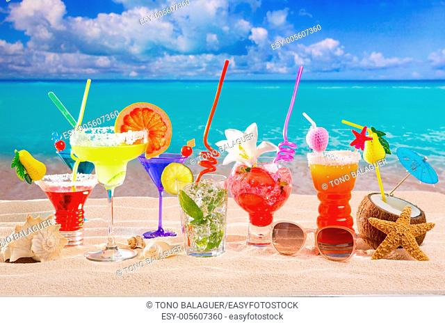 Colorful tropical cocktails at beach on white sand and turquoise water