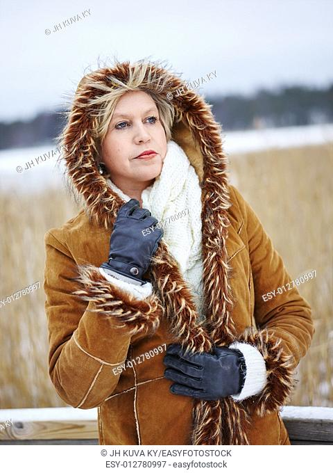 Close up, fashionable mature adult woman wearing winter clothes, frozen sea and reeds on background. South Finland in January