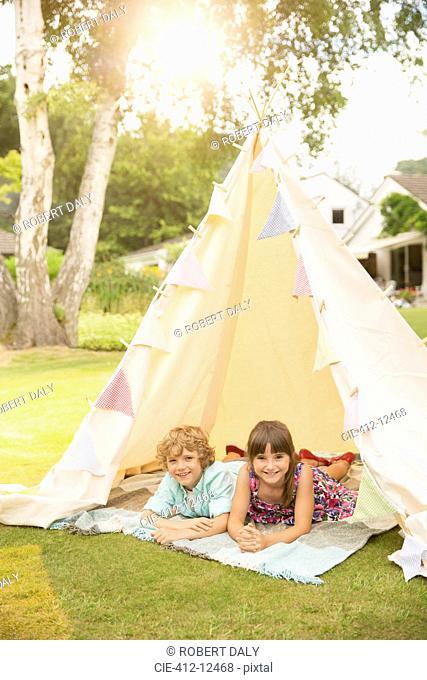 Children laying in teepee in backyard