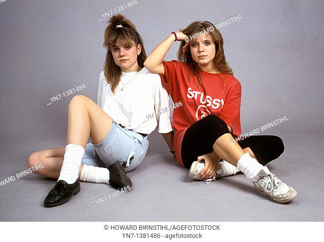 two teenage girls sitting on the floor of the studio posing for the camera but not showing a lot of enthusiasm