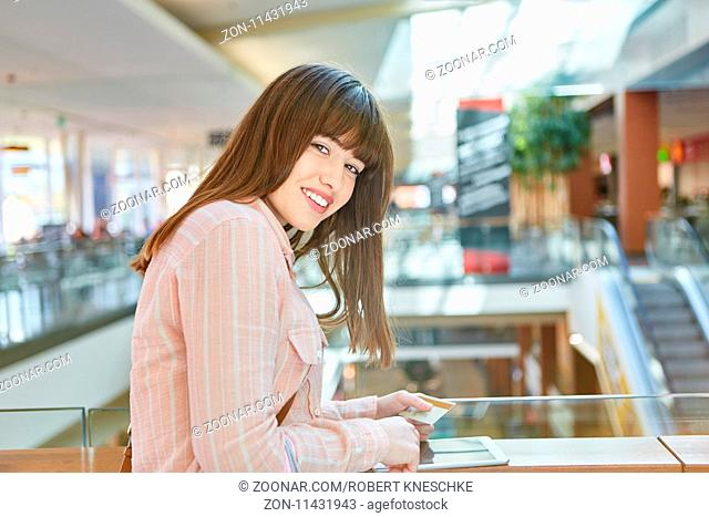 Junge Frau macht online Shopping mit Tablet Computer im Einkaufszentrum