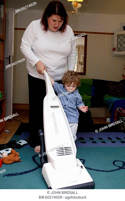 Mother vacuuming with her toddler son helping