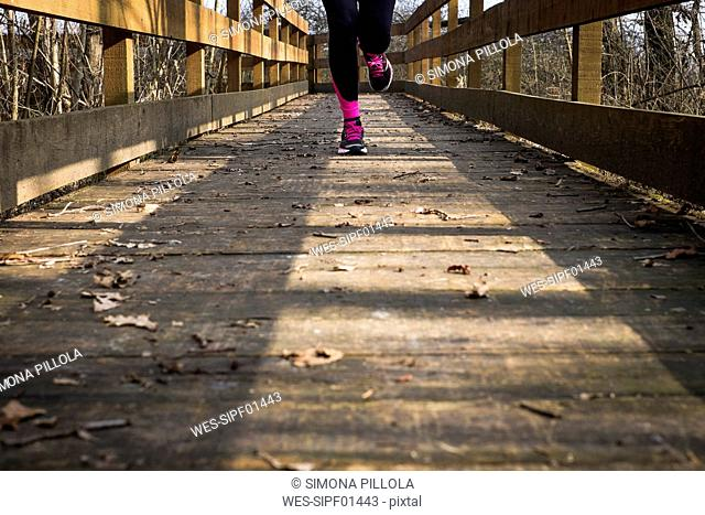 Close-up of woman running on a wooden bridge
