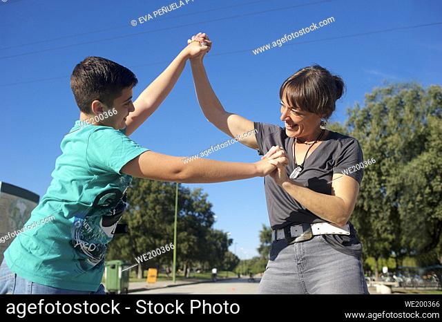 Mother with her son playing kick scooter in the park