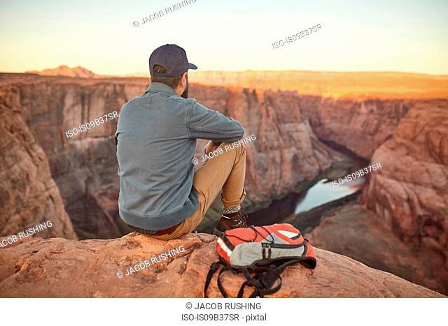 Man sitting on rock, looking at view, rear view, Page, Arizona, USA