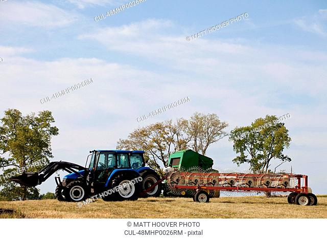Farmer driving tractor and thresher