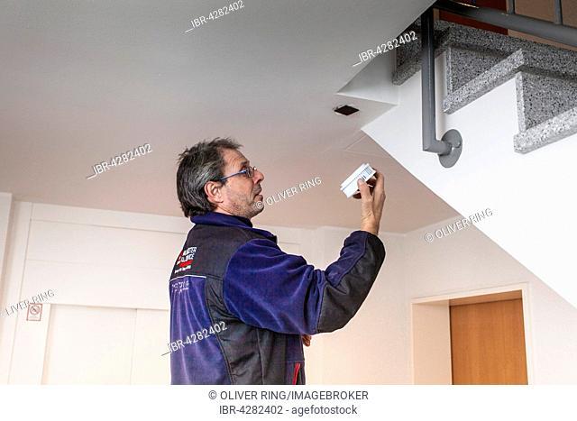 Caretaker with smoke detector in a stairwell, Düsseldorf, North Rhine-Westphalia, Germany