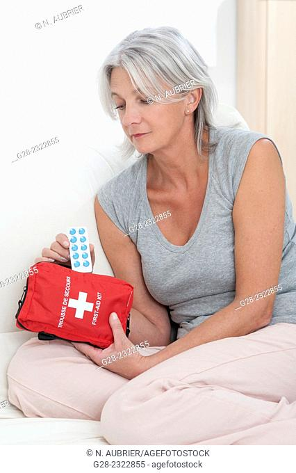Beautiful mature woman sitting on her bed and taking tablets out of a red first aid kit