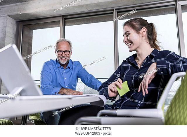 Smiling mature businessman and young woman with tablet in conference room in office
