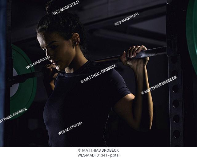 Young woman lifting barbell in power rack