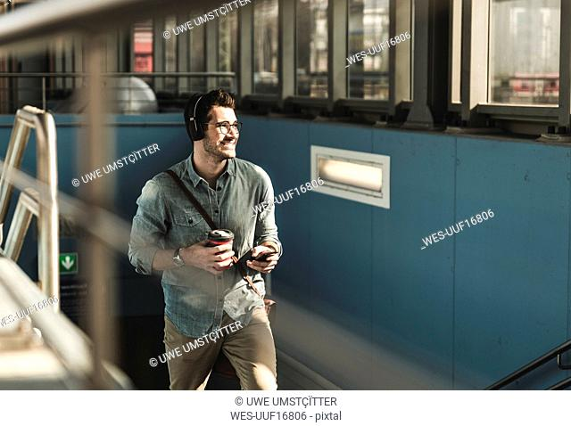 Smiling young man with headphones, cell phone and takeaway coffee walking at the station