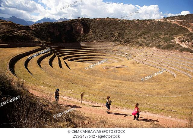Tourists walking on the terraces at Moray Ruins of the ancient Inca empire, Cusco Region, Peru, South America