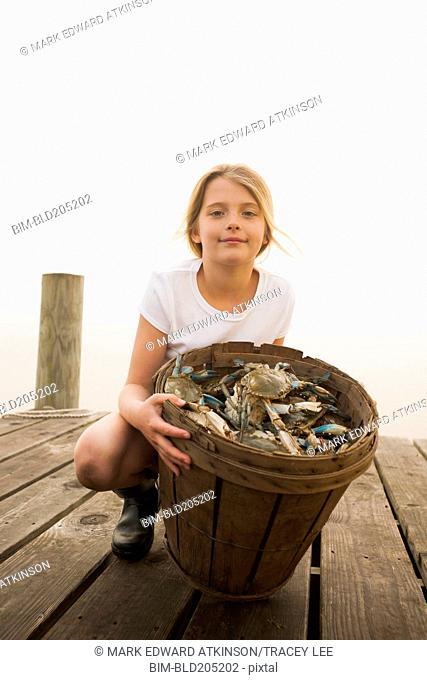 Caucasian girl holding basket of crabs