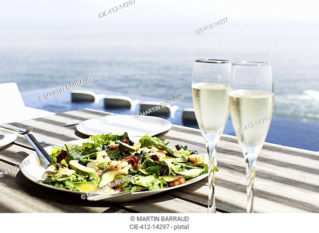 Plate of salad and glasses of champagne on table outdoors