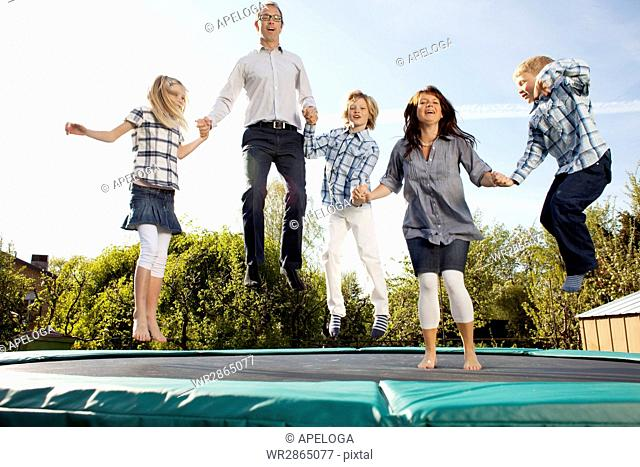 Happy family jumping on trampoline while holding hands in back yard against sky during sunny day