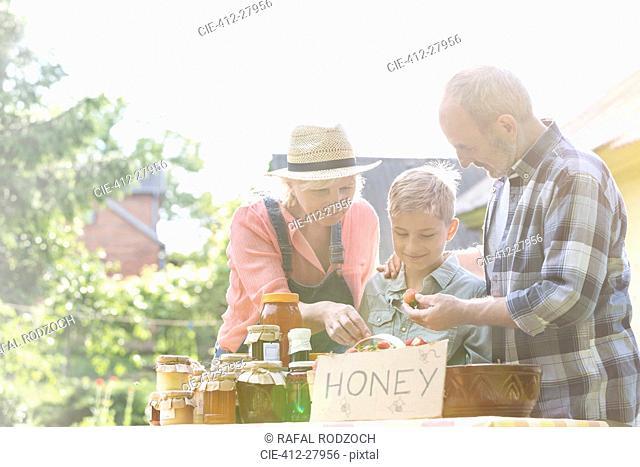 Grandparents and grandson selling honey at farmer's market stall