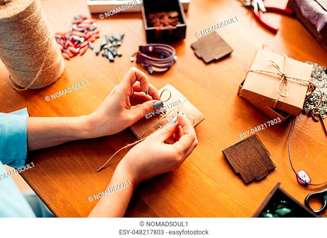 Female person tie a bow on a gift box, needlework accessories, top view. Handmade jewelry on wooden table, bijouterie making