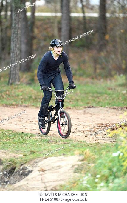Teenager with bmx bike in forest