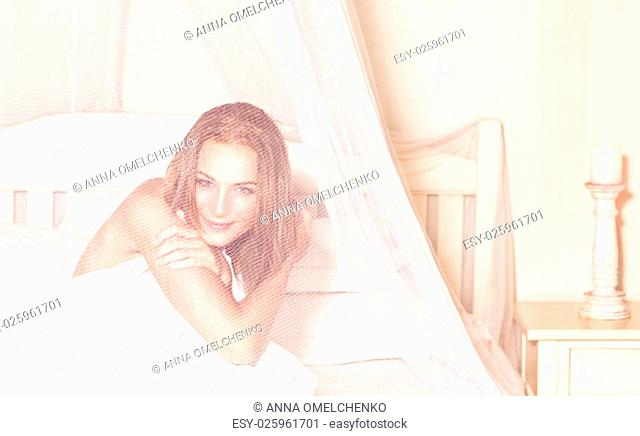 Portrait of gentle romantic woman sitting in the bed under gentle transparent valance, spending weekend in luxury spa hotel, enjoying rest and relaxation