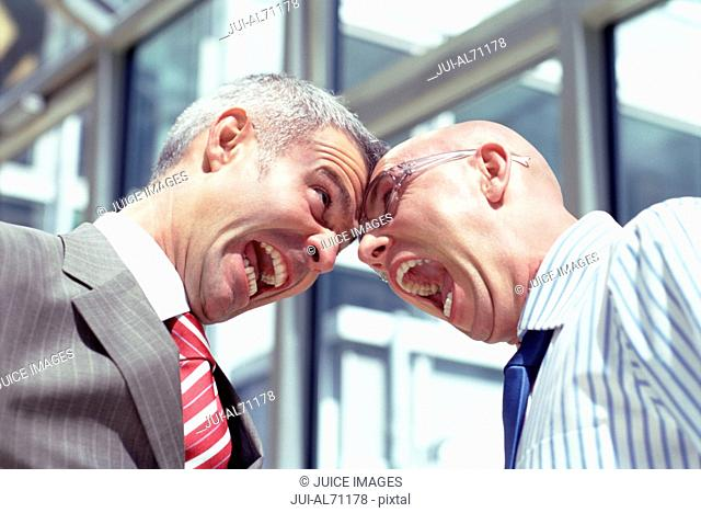 View of two businessmen making funny faces