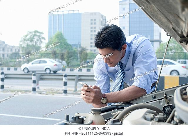 Businessman leaning on a broken down car and using mobile phone, Gurgaon, Haryana, India