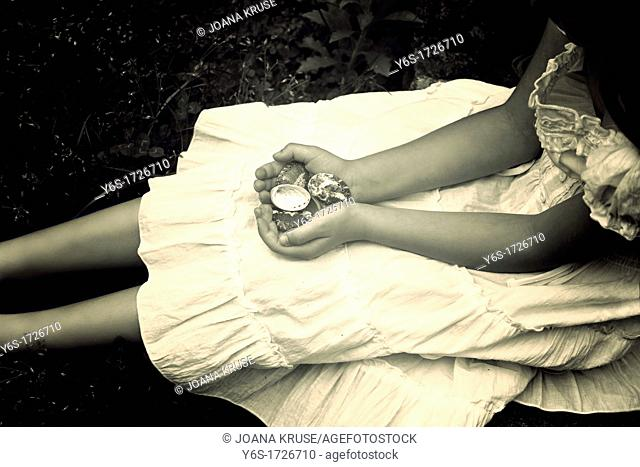 a girl lying in the grass and holding shells in her hands