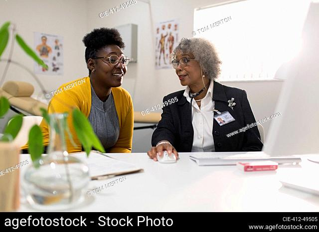 Female doctor meeting with patient at computer in doctors office